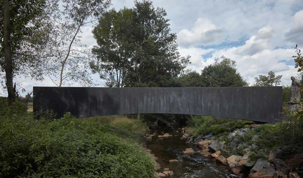 Impacto contextual: puente peatonal de concreto se funde con el paisaje