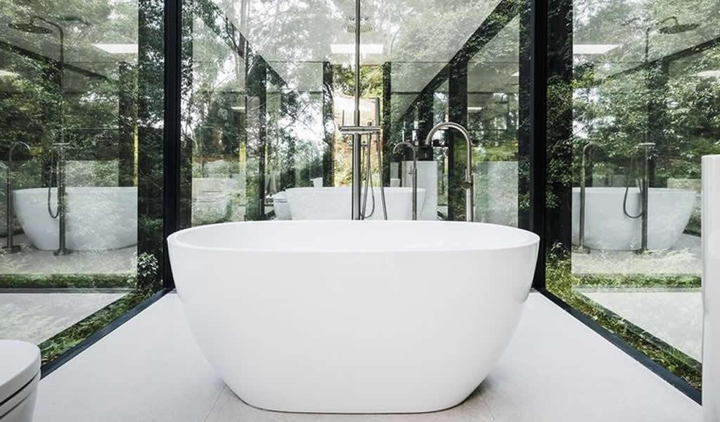 Un baño oculto tras paredes de espejo en pleno bosque